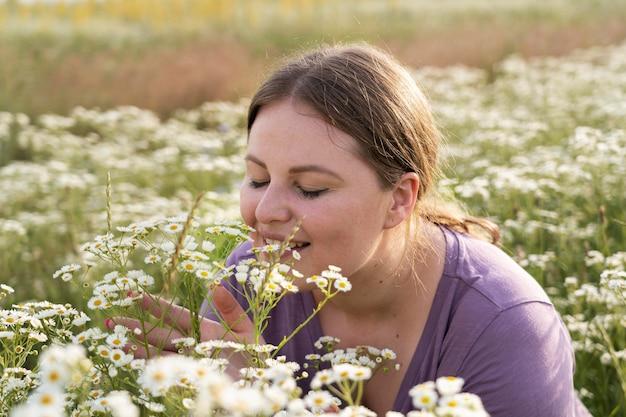 Cerrar mujer oliendo flores