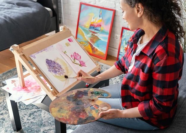 Cerrar mujer pintando en casa