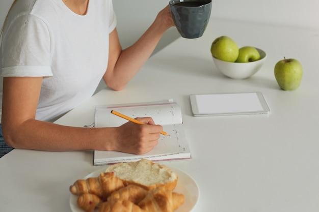 Cerrar mujer planeando su día, mantiene una taza gris con un poco de líquido