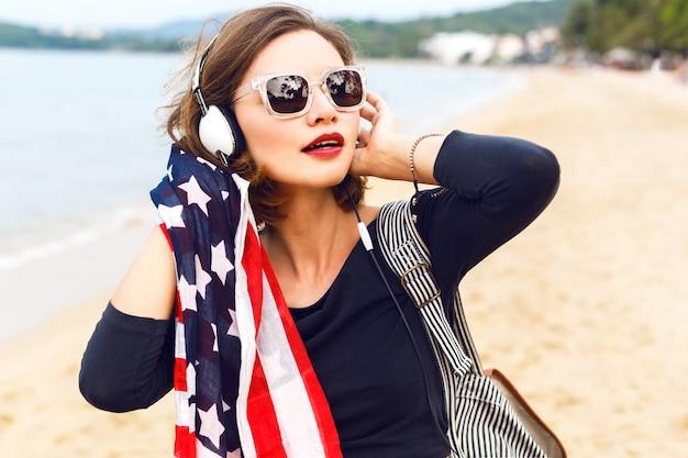 Cerrar mujer posando en la playa escuchando música en sus elegantes auriculares grandes