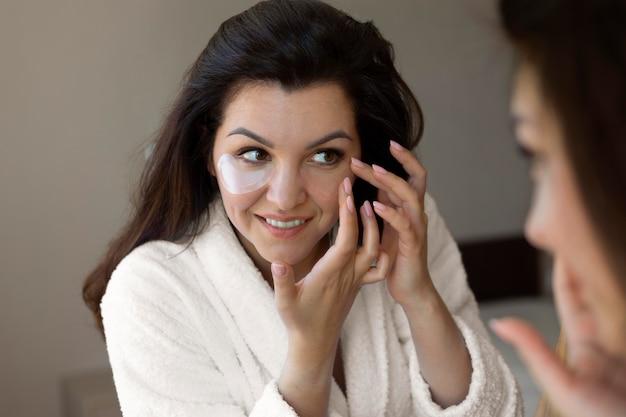 Cerrar mujer sonriente aplicando parche en el ojo