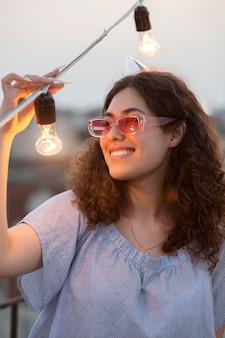 Cerrar mujer sonriente con bombillas