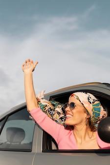 Cerrar mujer sonriente viajando en coche