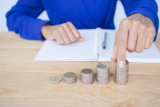Cerrar mujer sosteniendo moneda con pila de efectivo y libro, lápiz sobre mesa de madera
