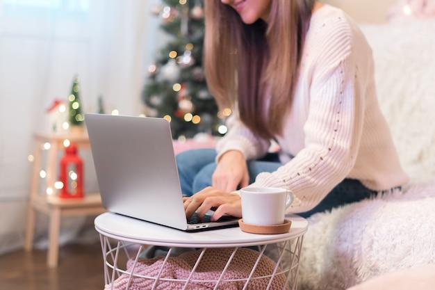 Cerrar mujer con taza de café escribiendo en el portátil