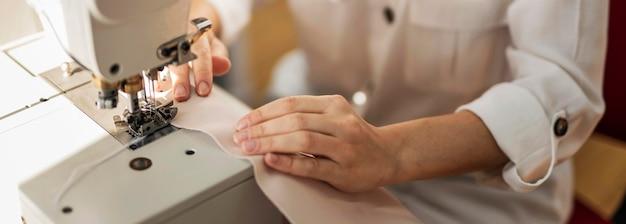 Cerrar mujer trabajando con máquina de coser