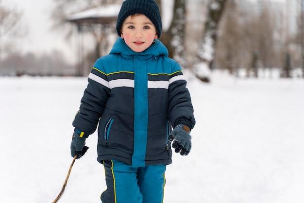 Cerrar n niño feliz jugando en la nieve.