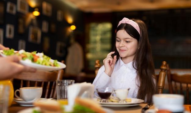 Cerrar niña sonriente en la mesa