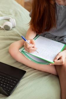 Cerrar niña tomando notas en la cama