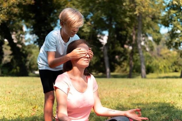 Cerrar niño cubriendo los ojos de la mujer