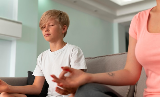 Cerrar niño y mujer meditando