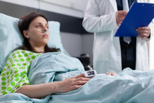 Cerrar paciente acostado en la cama con pulso de monitor de frecuencia cardíaca de dedo