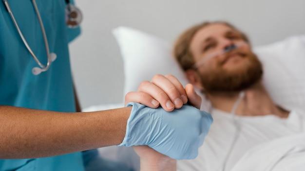 Cerrar paciente y trabajador de la salud tomados de la mano