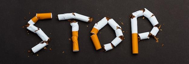 Cerrar palabra detener texto deletreado de la pila de cigarrillos o tabaco