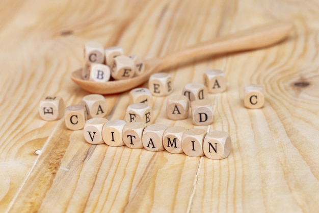 Cerrar palabra de vitaminas hecha de letras de madera en la mesa y abcde en la cuchara de madera