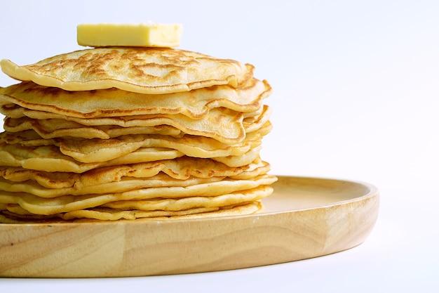 Cerrar panqueques y mantequilla en placa de madera con fondo blanco