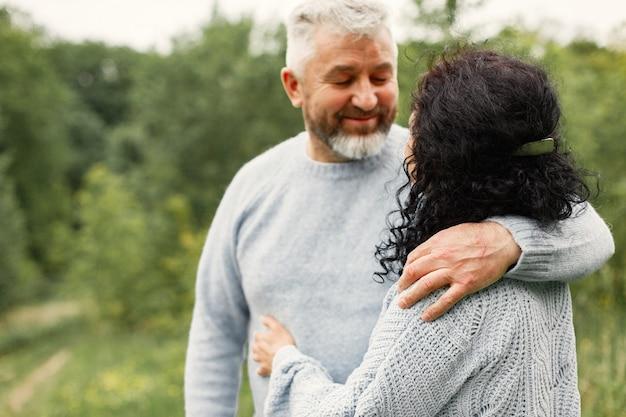 Cerrar pareja romántica de pie en el parque de otoño y abrazar durante el día