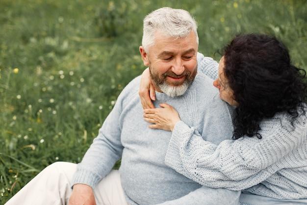 Cerrar pareja romántica sentada en el parque de otoño y abrazarse durante el día
