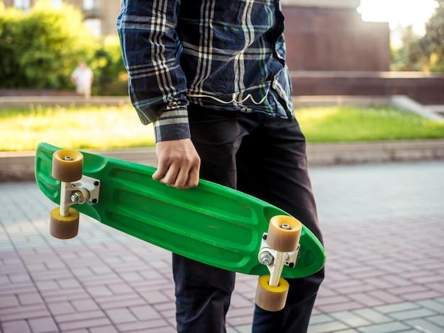 Cerrar parte del cuerpo del hombre joven caminando en la ciudad con el nuevo y moderno tablero de centavos de skate