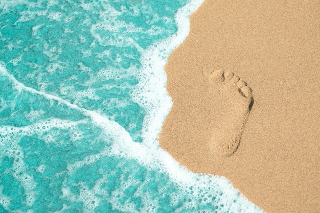 Cerrar paso de pie en la arena en la playa