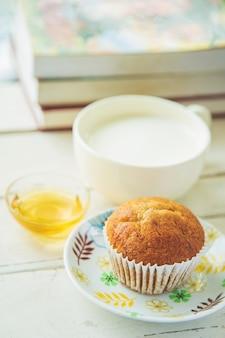 Cerrar pastel de plátano en plato blanco con miel y una taza de leche y libros