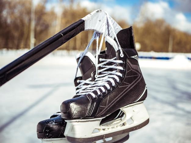 Cerrar patines de hockey colgar en el palo en la pista de hielo