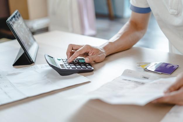 Cerrar persona calculando gastos mensuales y deudas de tarjetas de crédito.