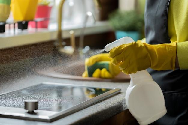 Cerrar persona con guantes de goma amarillos limpiando la casa, limpia la encimera de la cocina con detergente en aerosol, lava la estufa de inducción con una esponja