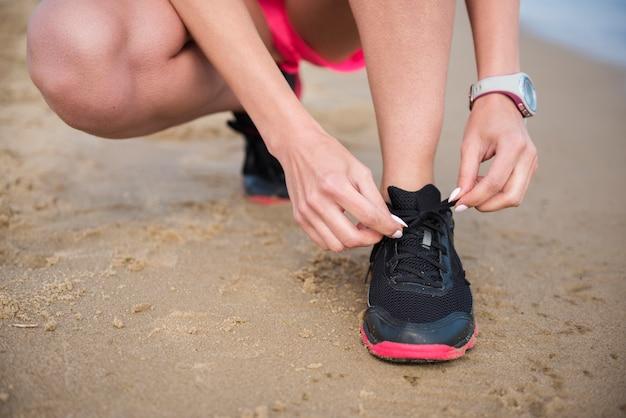 Cerrar en la persona joven encajar atando la lanza del zapato