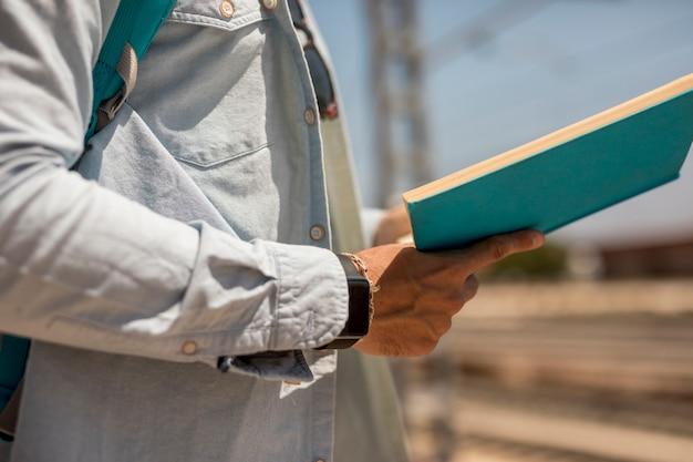Cerrar persona sosteniendo el libro en la estación de tren