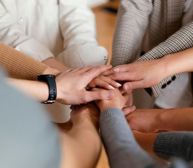 Cerrar personas cogidas de la mano en terapia