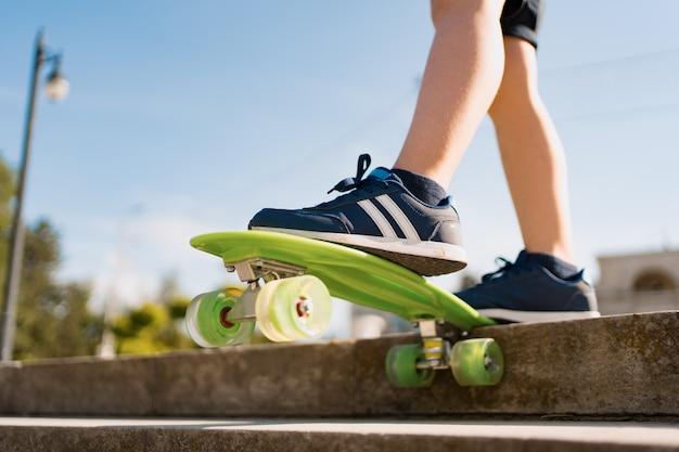 Cerrar las piernas en zapatillas azules montando en patineta verde en movimiento. estilo de vida urbano activo de juventud, formación, hobby, actividad. deporte activo al aire libre para niños. niño en patineta.