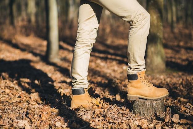 Cerrar las piernas en los zapatos de rastreo del hombre hipster que viaja en el bosque de otoño, turista activo, explorando la naturaleza en la estación fría, calzado