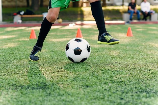 Cerrar los pies del futbolista pateando la pelota sobre el césped.