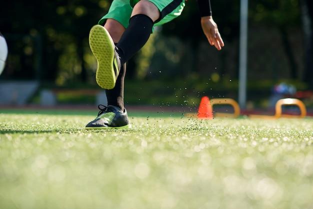 Cerrar los pies del futbolista pateando la pelota sobre el césped