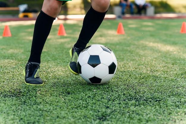 Cerrar los pies del futbolista pateando la pelota sobre la hierba verde.