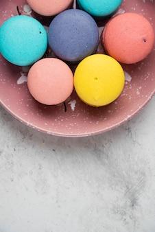 Cerrar placa de macarons pastel sobre superficie blanca.
