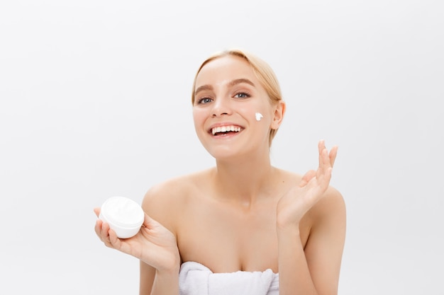 Cerrar el retrato de la belleza de una hermosa mujer desnuda mitad riendo aplicar crema facial y mirando lejos