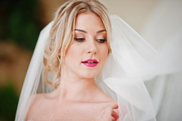 Cerrar retrato de cara hermosa novia rubia posó en el gran salón de bodas increíble