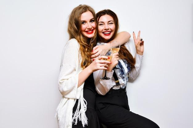 Cerrar un retrato divertido de chicas guapas divirtiéndose en una fiesta increíble, maquillaje brillante, pelos largos, sosteniendo copas con champán, bonito retrato de mejores amigos, imagen con flash.