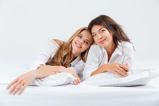 Cerrar el retrato de dos hermosas mujeres jóvenes acostados juntos en la cama con sábanas blancas