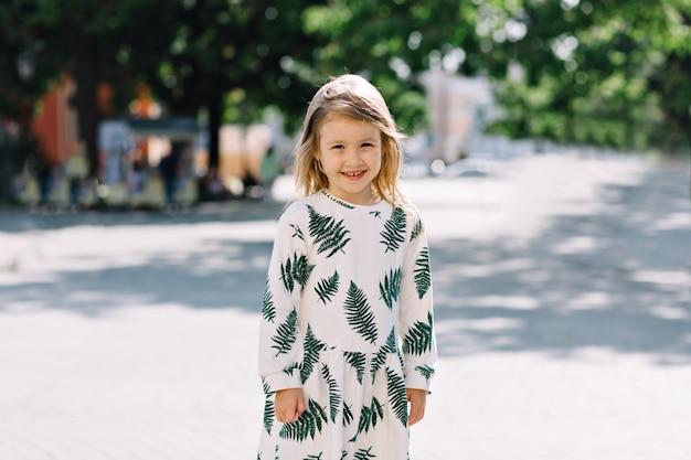 Cerrar el retrato exterior de una niña bonita sonriente en vestido de verano con una sonrisa maravillosa divirtiéndose y mirando al frente
