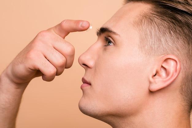 Cerrar retrato de hombre guapo poniendo lentes de contacto en su ojo aislado beige