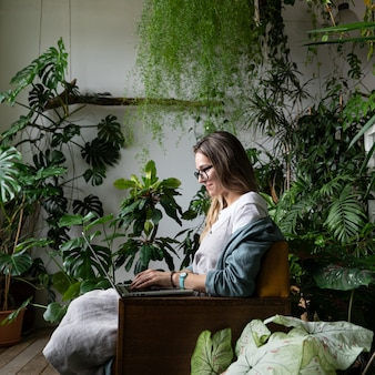 Cerrar retrato de jardinera sonriente con gafas, vestido de lino, sentado en una silla en invernadero, usando la computadora portátil y hablando en una llamada web rodeada de plantas exóticas. jardinería doméstica, autónomo