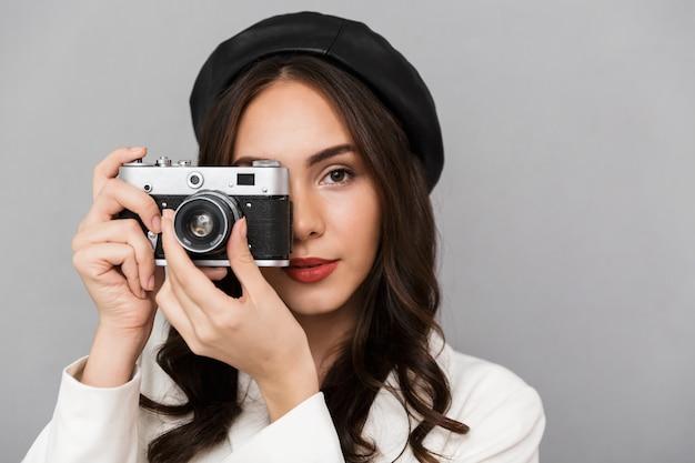 Cerrar el retrato de una joven y bella mujer vestida con chaqueta sobre fondo gris, tomando fotografías con cámara de fotos