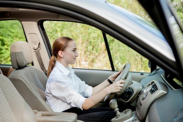 Cerrar retrato de mujer de aspecto agradable con expresión positiva alegre, satisfecho con viaje inolvidable en coche, se sienta en el asiento del conductor. gente, conducción, concepto de transporte