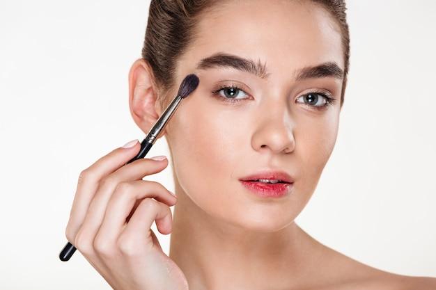 Cerrar retrato de mujer hermosa con piel sana aplicando maquillaje pintura ojos con pincel