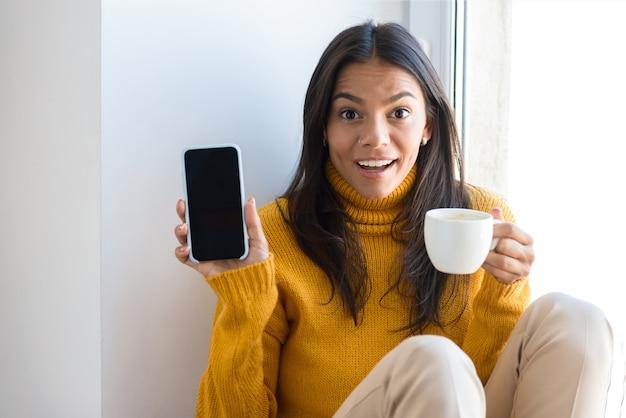 Cerrar el retrato de una mujer joven feliz vestida con un suéter sentado en la ventana en el interior, sosteniendo una taza de té, mostrando el teléfono móvil de pantalla en blanco
