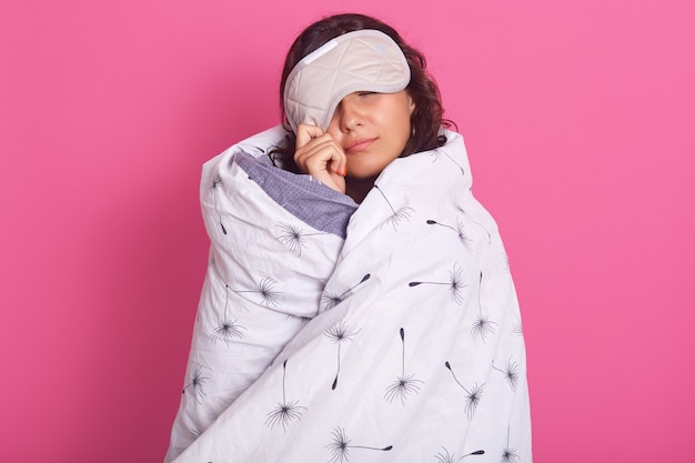 Cerrar retrato de mujer morena asomando de máscara para dormir, no quiere despertarse, mantiene los ojos cerrados, con una manta blanca