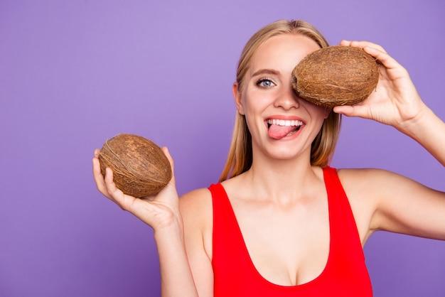 Cerrar retrato de niña encantadora mostrando la lengua cerrando los ojos sosteniendo cocos